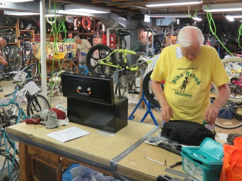 A Bike Rehab volunteer in a yellow shirt looks through a bag on a worktable, surrounded by bikes being rehabbed.