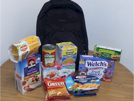 A child's backpack full of small food items to eat for the weekend.