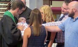 Infant baptism with pastors and parents.