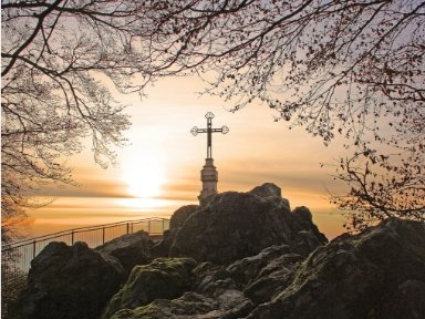 Photo of cross on a hill as the sun is rising.