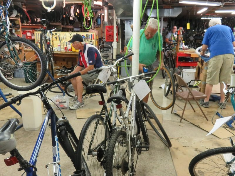 Bike Rehab volunteers fix bikes in a basement filled with tools and work tables.