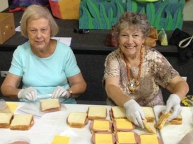 Sandwich Ministry volunteers make sandwiches in an assembly line.