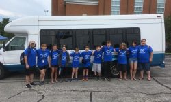 Photo of Manchester Youth in front of a white transportation van.