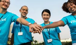 Four volunteers of varying ethnicities touch hands in a team huddle.