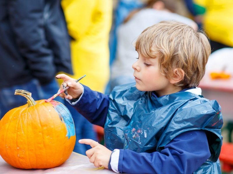 Little boy painting a pumpkin.