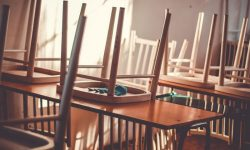 Empty classroom with chairs stacked on tables.