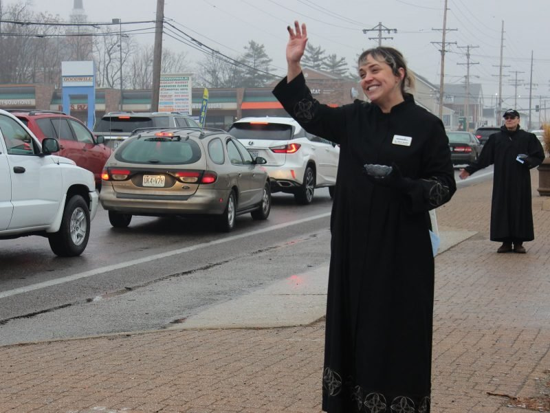 Pastor Winter Hamilton waves to ongong traffic as she offers the imposition of ashes on Ash Wednesday.