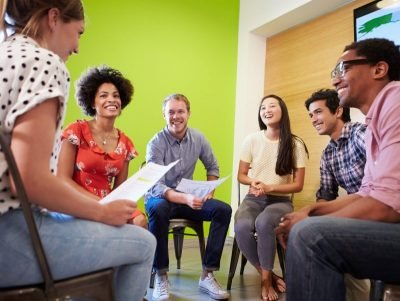 Photo of a group discussion with young adults in a semi-circle.
