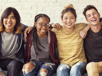 Photo of young adults sitting with hands on shoulders.