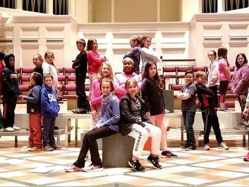 Photo of children's choir rehearsing a musical.