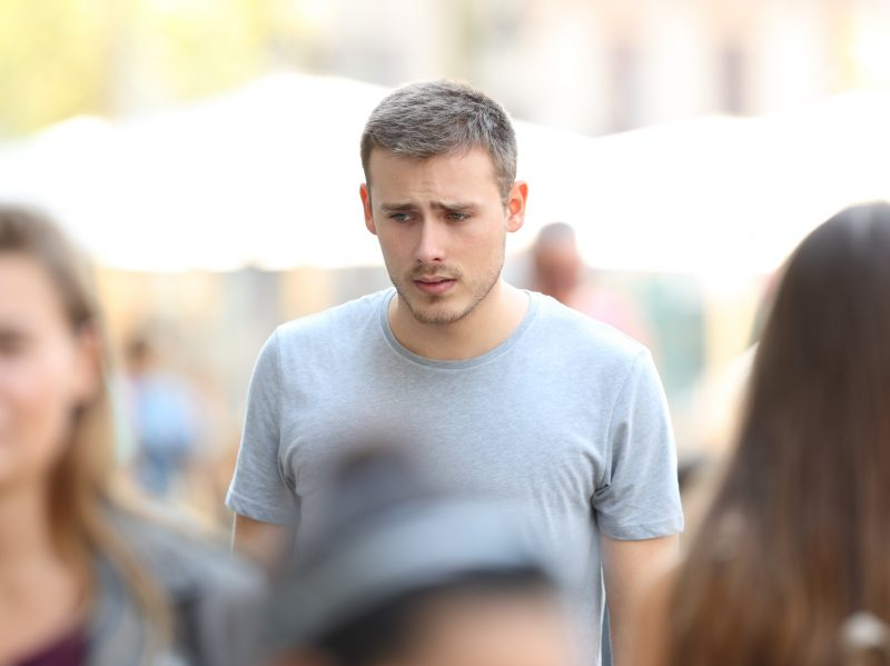 Photo of a man in a crowd looking depressed.