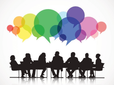 A group of silhouetted figures gather at a table to share their ideas, represented as a rainbow of speech bubbles.