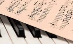 Photo of piano keys with music notes lying on top