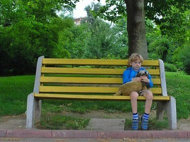 Photo of young boy sitting on a park bench by himself.