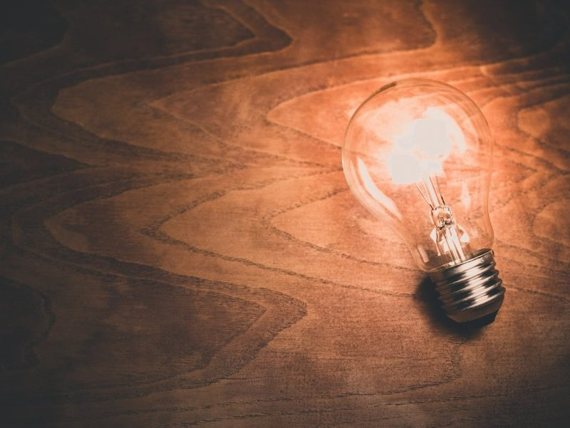 Light bulb turned on lying on a beautiful woodgrain table.