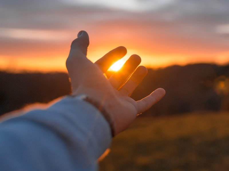 Photo of a hand reaching out toward the sunset.