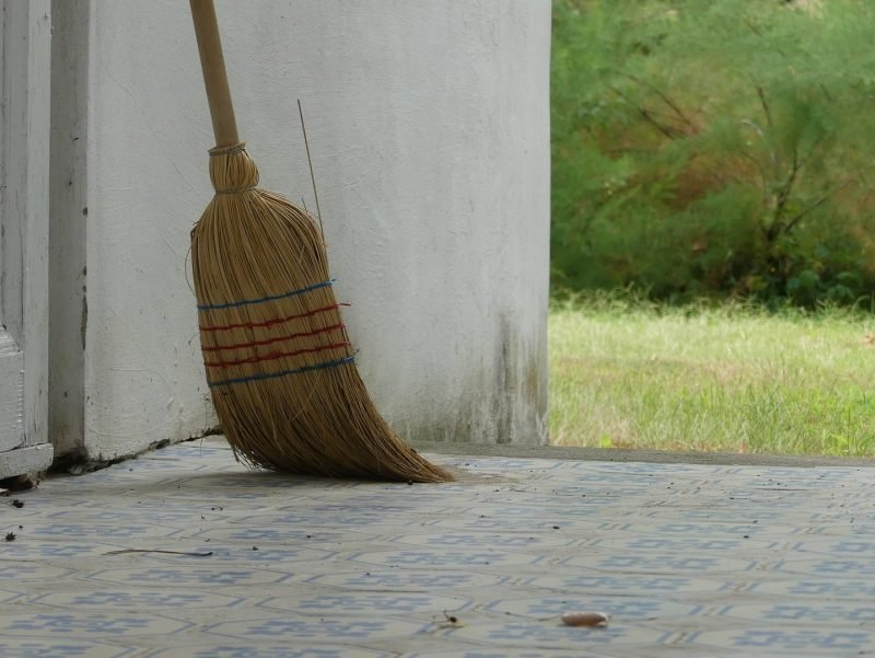 Photo of a broom sitting outside on a porch ready for use.