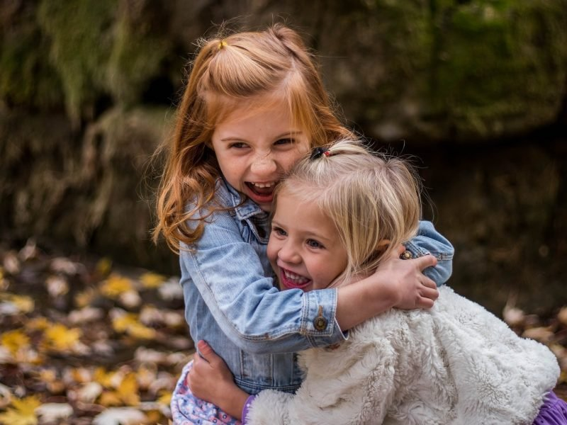 Two small girls hugging each other, not holding back.