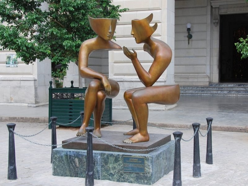 Photo of sculpture showing two people seated speaking with one another.