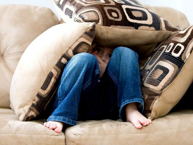 Photo of a child buried under couch pillows in fear.
