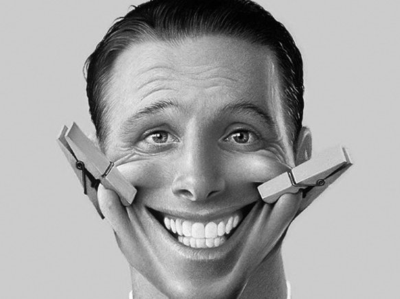 Image of a man with a fake smile pinned on with clothes pins at each side of his mouth.