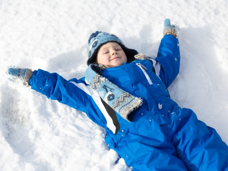 Child making a snow angel in the snow.