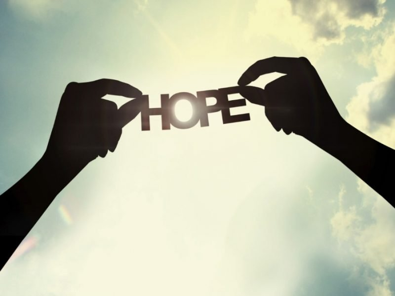 Photo of hands holding a paper cutout of the word Hope.