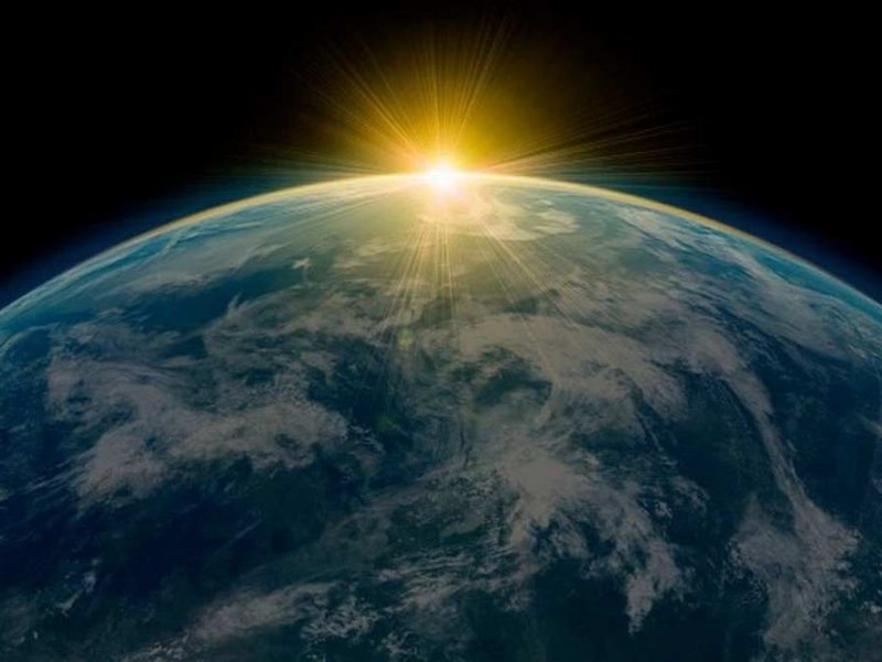 Photo of the light dawning over the outline of Earth in space.