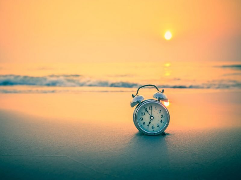 Photo of an alarm clock sitting on a beach with the sun rising.