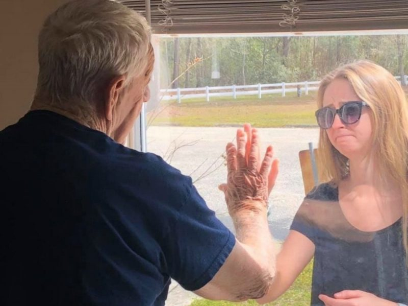 Man and woman with hands pressed against a glass barrier.