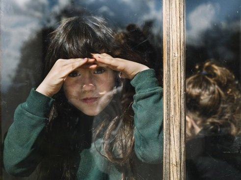 Young girl looking through a window.