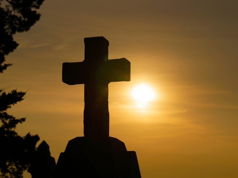 Photo of a cross with a sunset in the background.