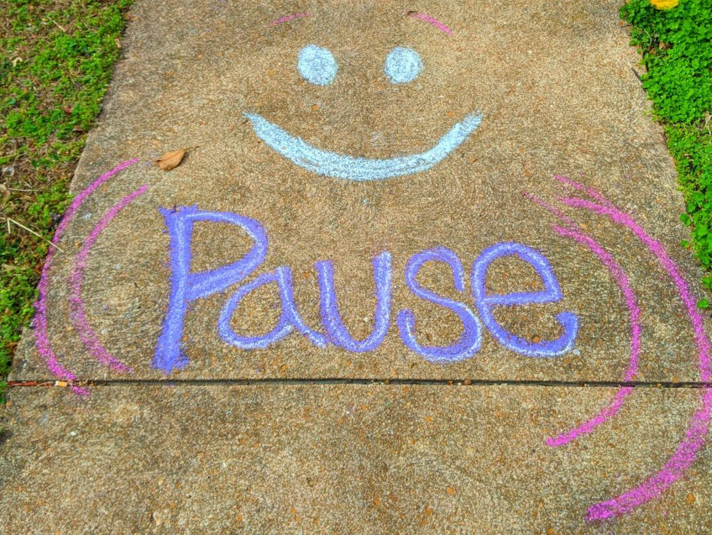Sidewalk chalk art with a smiley face and the word Pause underneath.