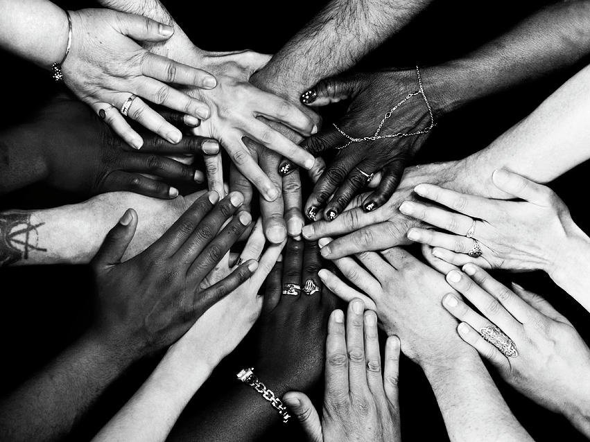 Photo of hands of many people placed on top of each other.
