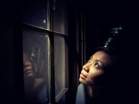 Woman prayerfully looking up out a window.