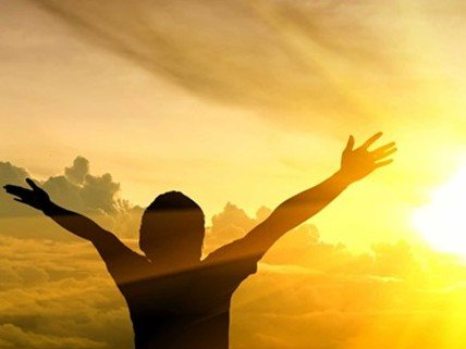 Person raising their hands up toward a dawning sun.