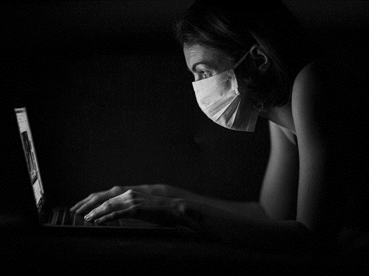 Photo of woman focused only on her computer, no one else.