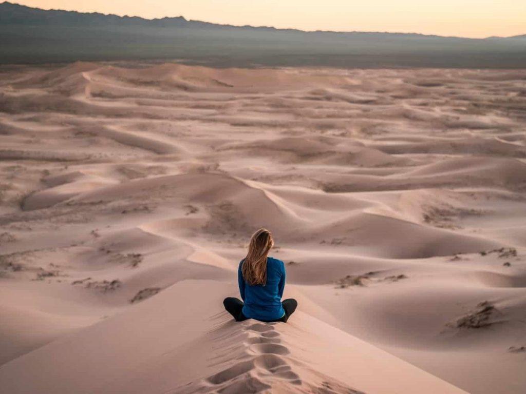 Woman sitting on desert sand overlooking the expanse.